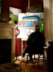 Artist Bobbi Pike sits at her easel as she puts the finishing touches on Old Betsy